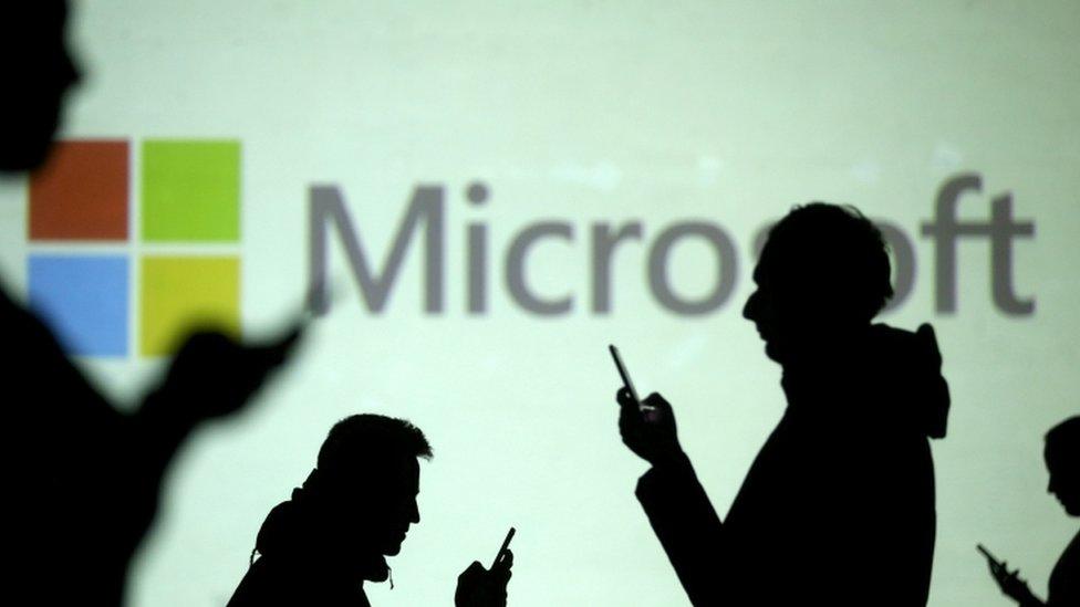 Personas manejan sus teléfonos junto a un panel de Microsoft.