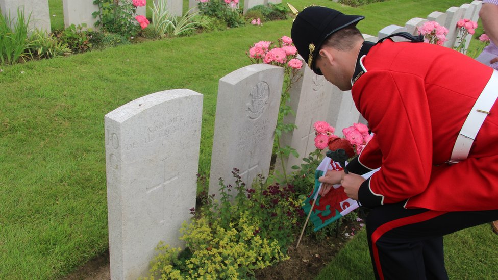 A member of the band of the Royal Welsh lays a flag at the grave of a Welsh soldier at Flatiron Copse cemetery