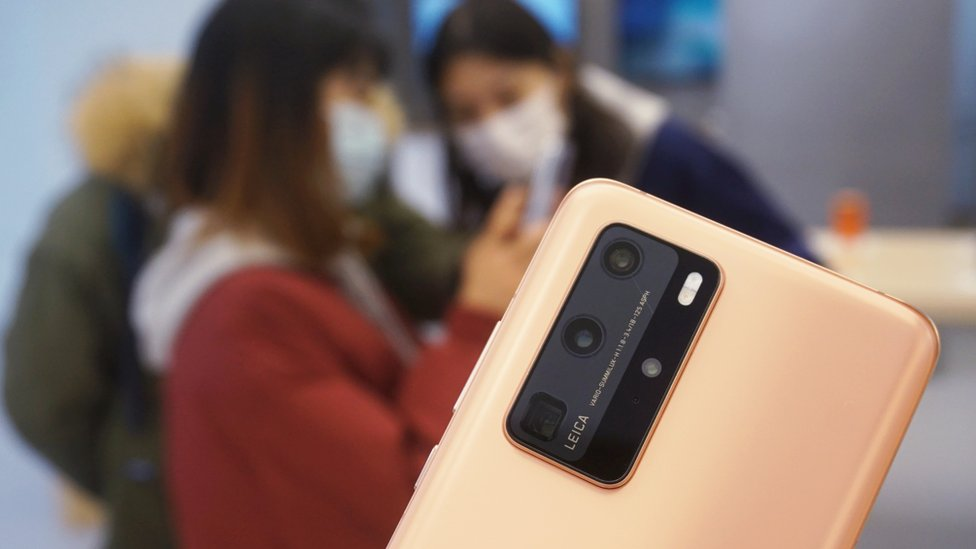 The rear panel of a Huawei P40 phone is seen in sharp focus, against a blurred background scene of customers trying out the phones