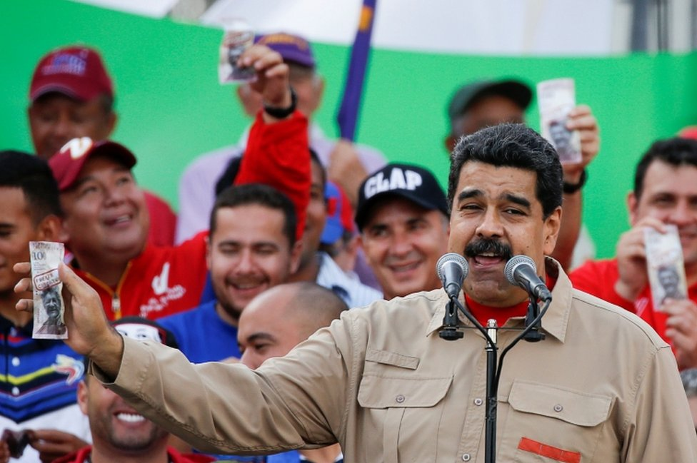 Venezuela's President Nicolas Maduro holds up a mock 100-bolivar bill depicting the president of the National Assembly Henry Ramos Allup, during a pro-government rally in Caracas, Venezuela December 17, 2016.