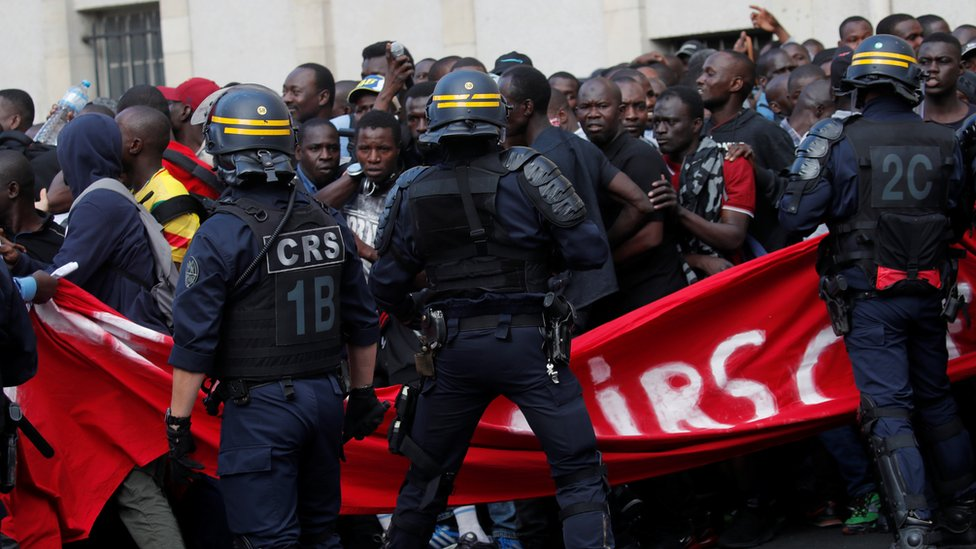 Undocumented migrants are surrounded by police after having occupied the Panthéon in Paris, 12 July 2019