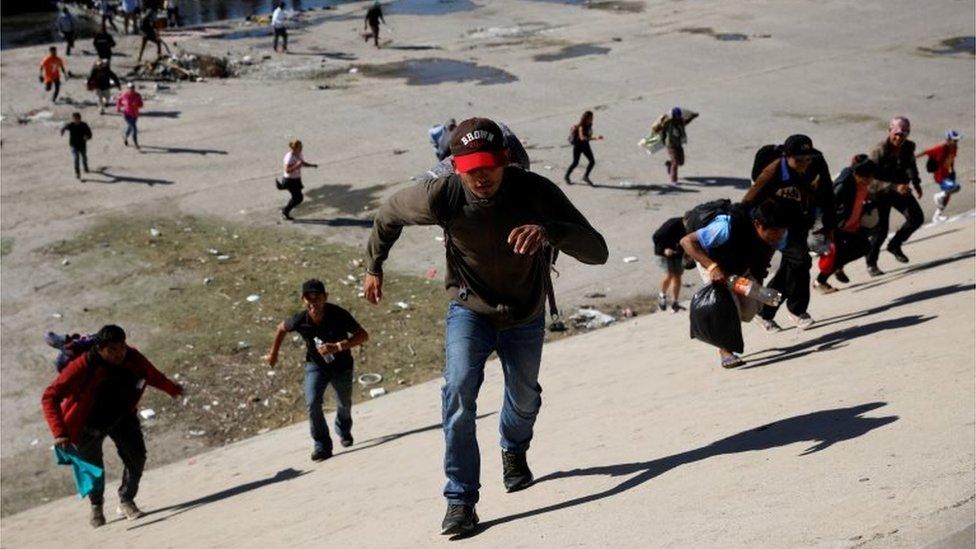 Migrants run across the Tijuana river to reach the border wall between the U.S. and Mexico in Tijuana, Mexico November 25, 2018.