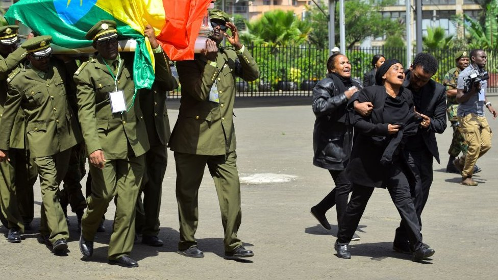 Woman weeps alongside coffins at the memorial service in Addis Ababa