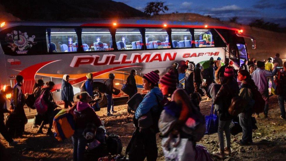 Venezolanos subiendo a un bus en Ecuador, huyendo de su país.