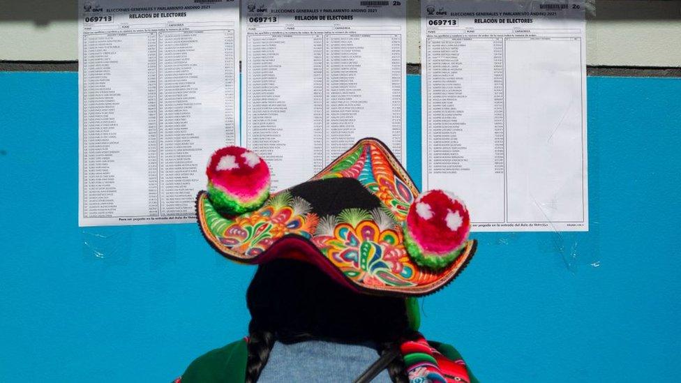 Mujer indígena frente a una lista de electores en un colegio electoral.
