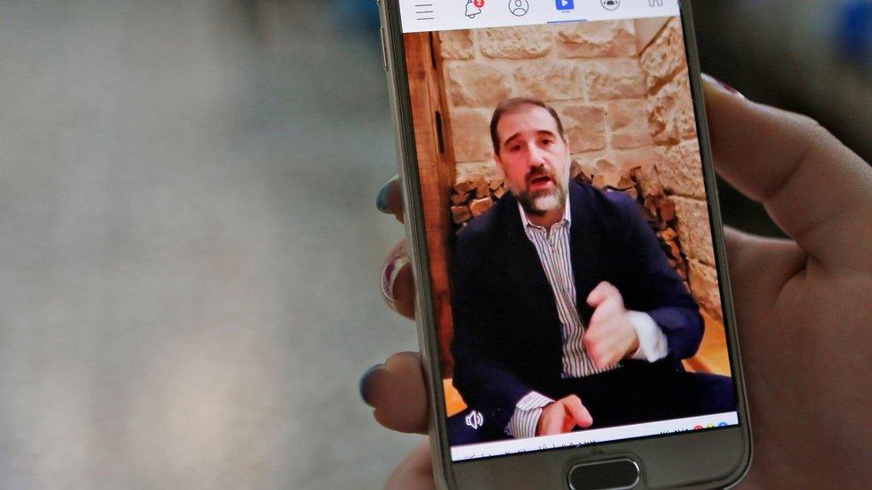 Una mujer mira un video en redes sociales en el que aparece Rami Makhlouf (11 de mayo de 2020)