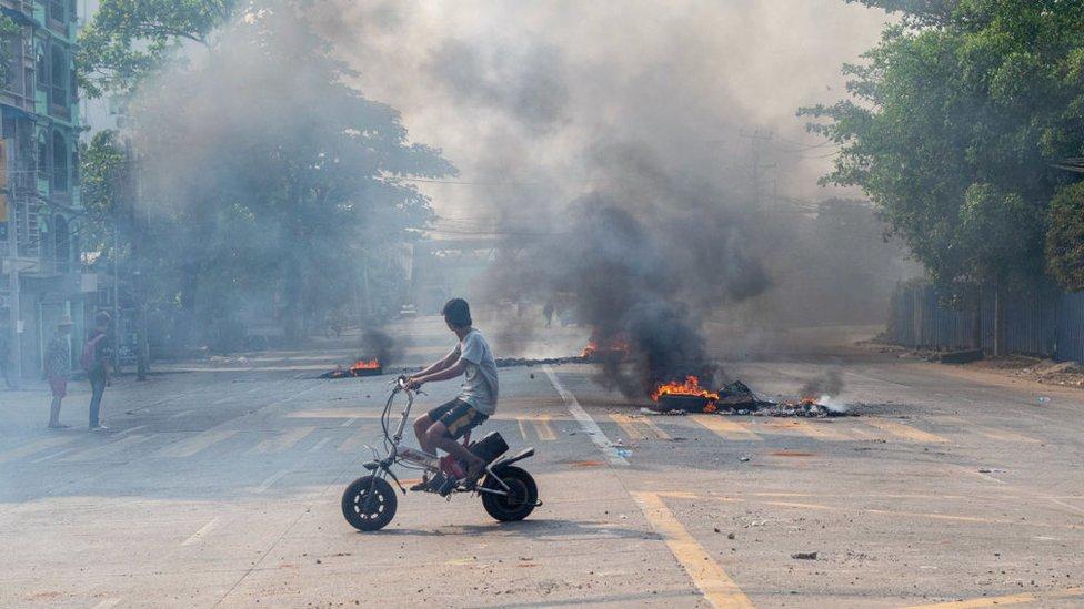 راكب دراجة نارية يمر بالقرب من إطارات محترقة في الشارع أثناء احتجاج على الانقلاب العسكري في ميانمار