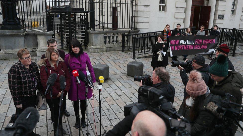 Sarah Ewart with her mother and Grainne Teggart of Amnesty International