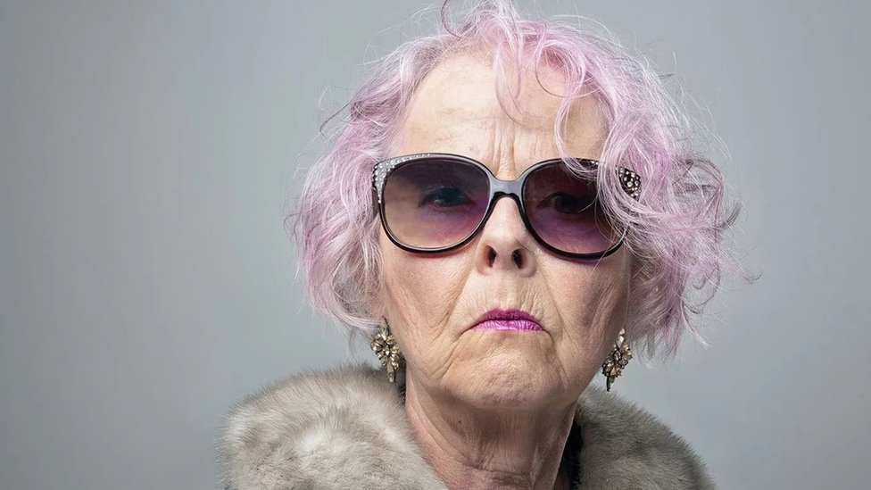 A woman with hair dyed purple and wearing sunglasses looks at the camera