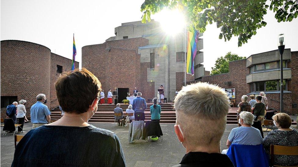 Parejas en una bendición afuera de una iglesia católica en Colonia.