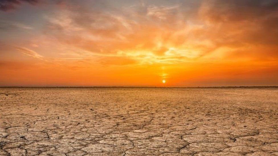 Puesta de sol en el horizonte y un terreno quebrado durante una sequía
