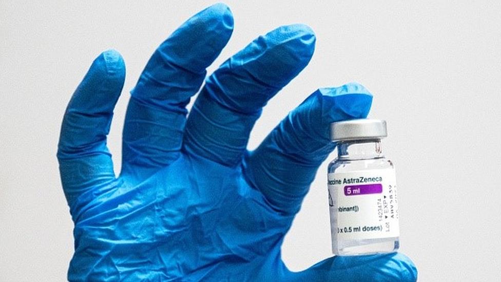 Mão com luva segura ampola de vacina de AstraZeneca e Universidade de Oxford