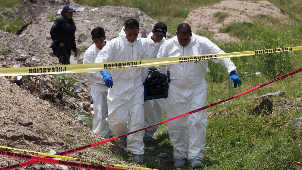 Policías ministeriales llevan un cuerpo de una fosa común en México.