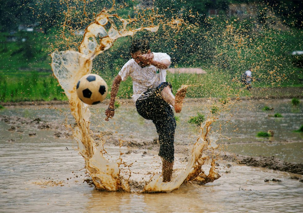 A man kicks a football as he takes part in an event celebrating National Paddy Day in Lalitpur, Nepal, June 29, 2018