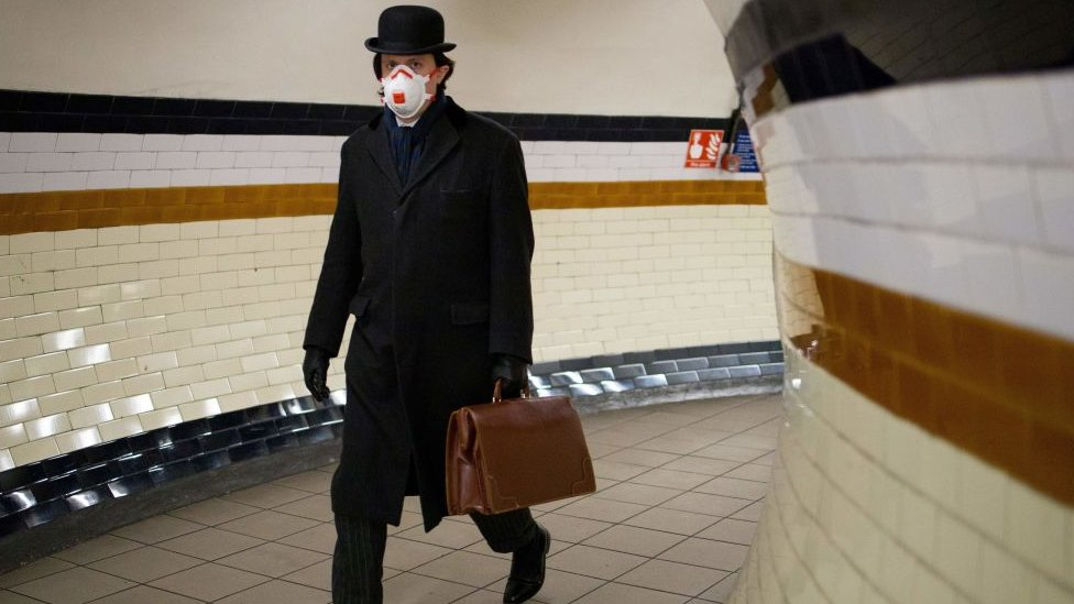 Commuter on the tube wearing face mask