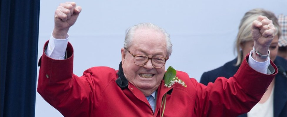 France's far-right political party Front National (FN) founder and honorary president, Jean-Marie Le Pen gestures on stage as FN's president Marine Le Pen looks on during the party's annual rally honouring Joan of Arc on Place de l'Opera, on 1 May 2015 in Paris, France.