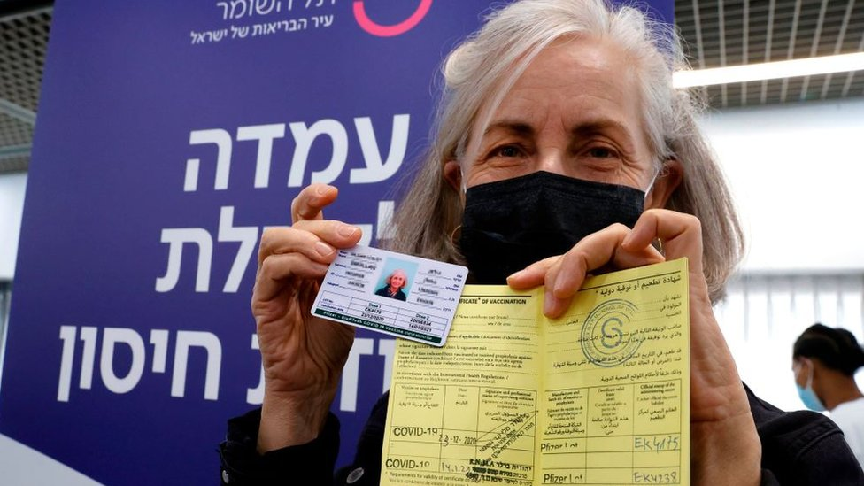 Una mujer en Israel muestra su certificado de vacunación