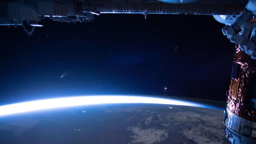 Cahaya komet itu dipotret bersama cakrawala timur dari Stasiun Antariksa Internasional pada 5 Juli.