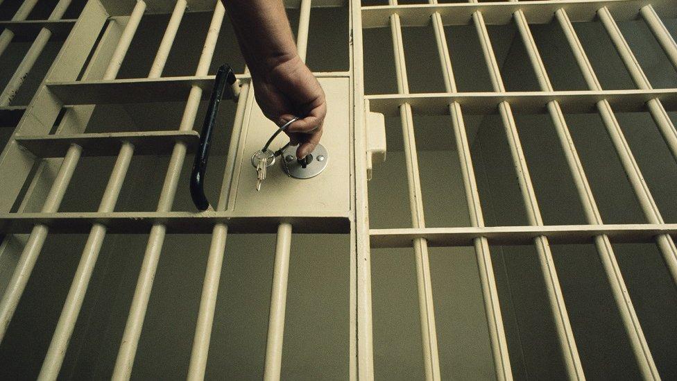 Mão fechando as grades de uma prisão