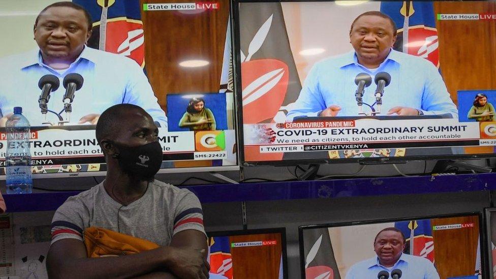 फेस मास्क पहनने वाला एक आदमी केन्या के राष्ट्रपति उहुरू केन्याटा के रूप में एक इलेक्ट्रॉनिक्स की दुकान के अंदर खड़ा है, जो टीवी स्क्रीन पर COVID-19 (उपन्यास कोरोनावायरस) महामारी पर देश को एक संबोधन देते हुए दिखाई देता है, और सरकार को बनाए रखने के लिए उपायों को बनाए रखता है और लागू करता है रोग का प्रसार, 27 जुलाई, 2020 को नैरोबी में