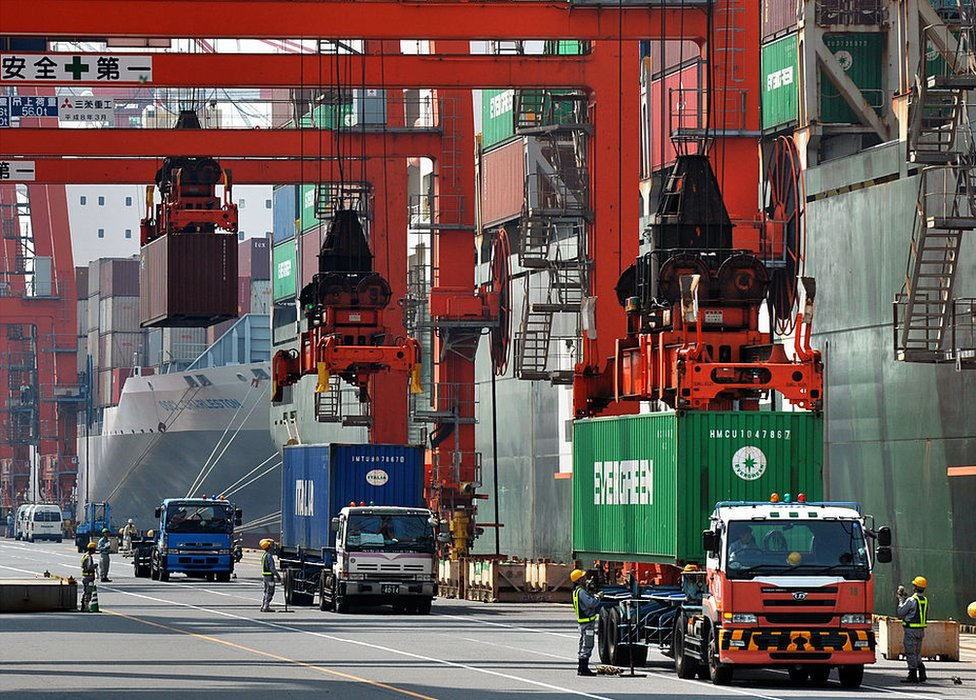 A cargo crane unloads containers from a ship at a quay in Tokyo in July 2012.