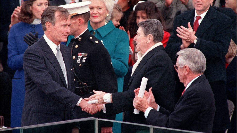 Former US President Ronald Reagan greets newly-inaugurated President George H W Bush as first lady Barbara Bush applauds during Bush's swearing-in ceremony, 20 January 1989, in Washington, DC.