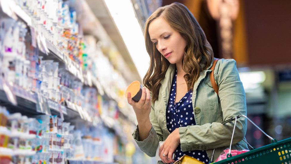 Mujer en un supermercado leyendo la etiqueta de un yogur