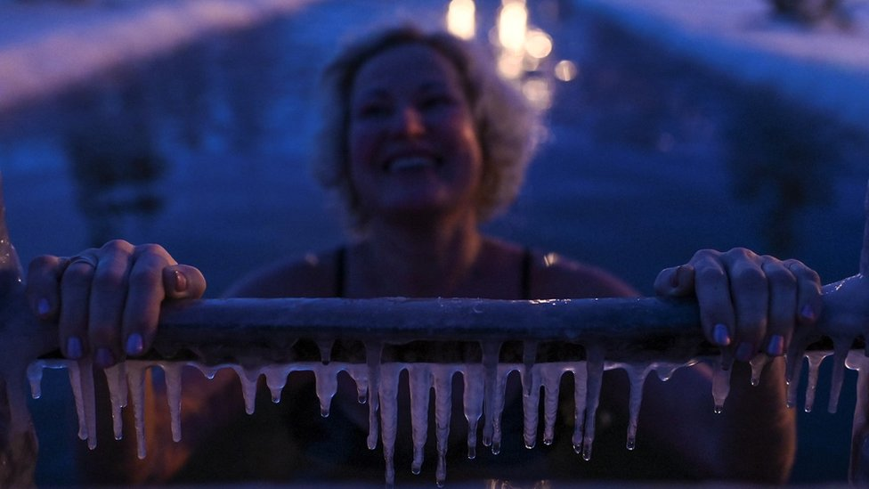 A woman takes a dip during celebrations of Orthodox Epiphany in Omsk