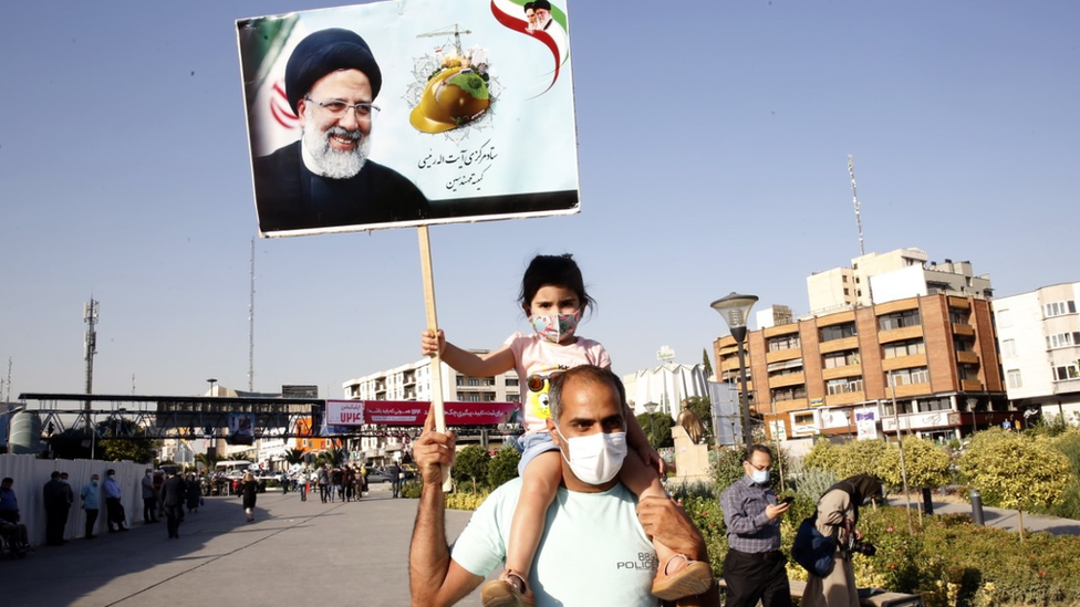 Girl on a man's shoulders holds up a poster of election candidate Ebrahim Raisi