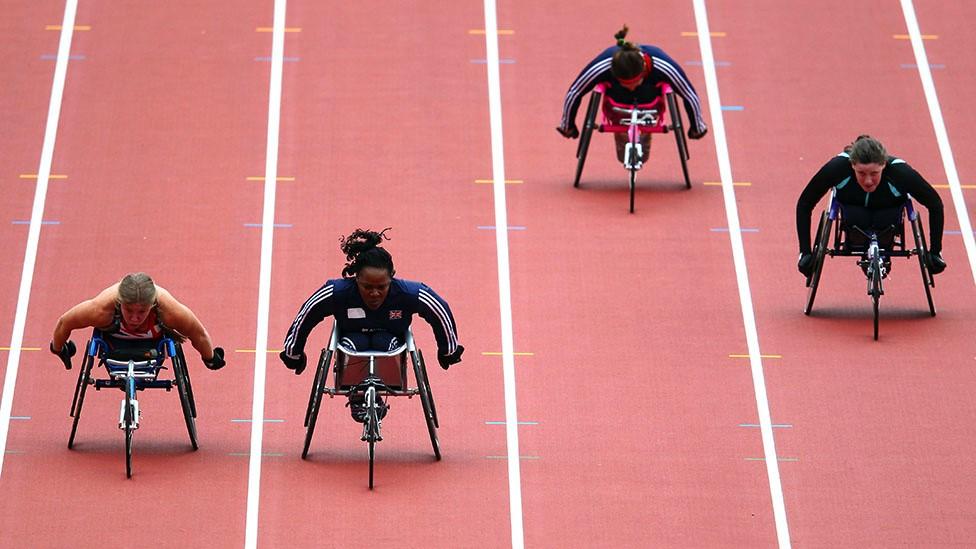Anne Wafula Strike racing in a wheelchair against three competitors