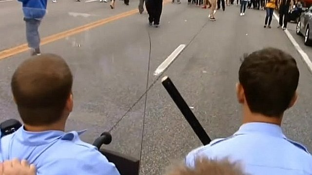 Unverified footage from behind police lines shows officers using shields to protect themselves from objects being thrown by protesters