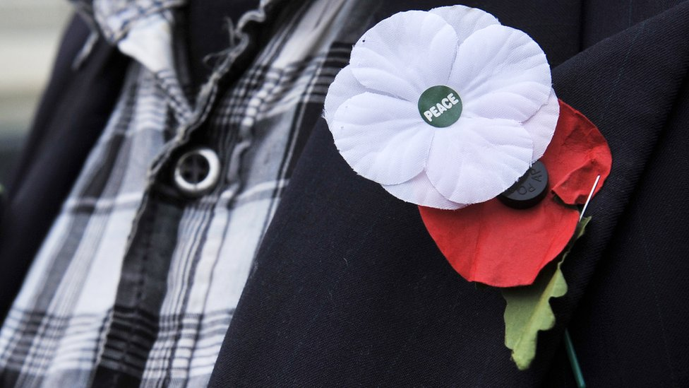 A white and red poppy worn alongside each other