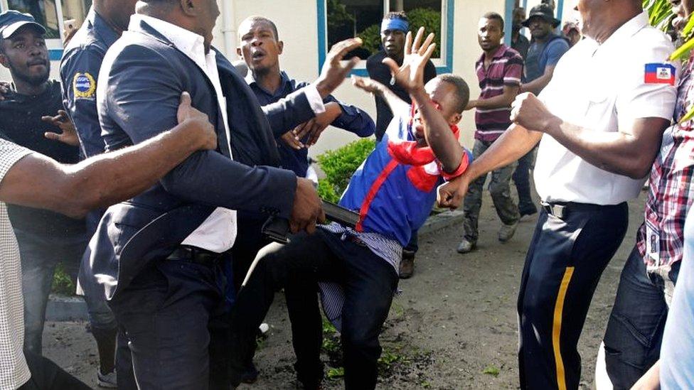 Haitian Senator Willot Joseph holds a gun as he pushes an opposition supporter in Port-au-Prince, Haiti