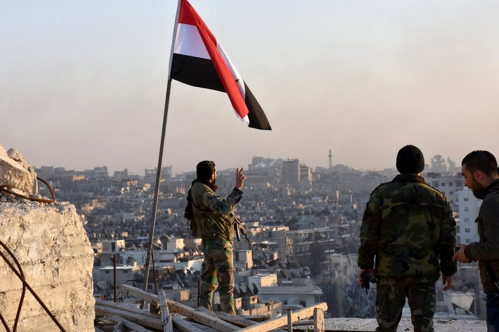 A Syrian government soldier makes a gesture under a Syrian national flag in Aleppo (28 November 2016)
