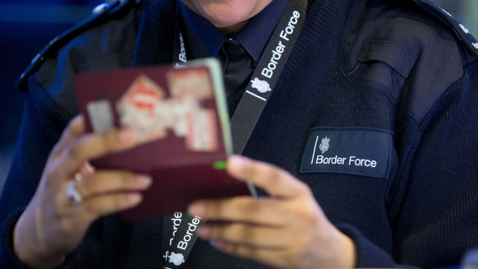 Border Force official with a passport