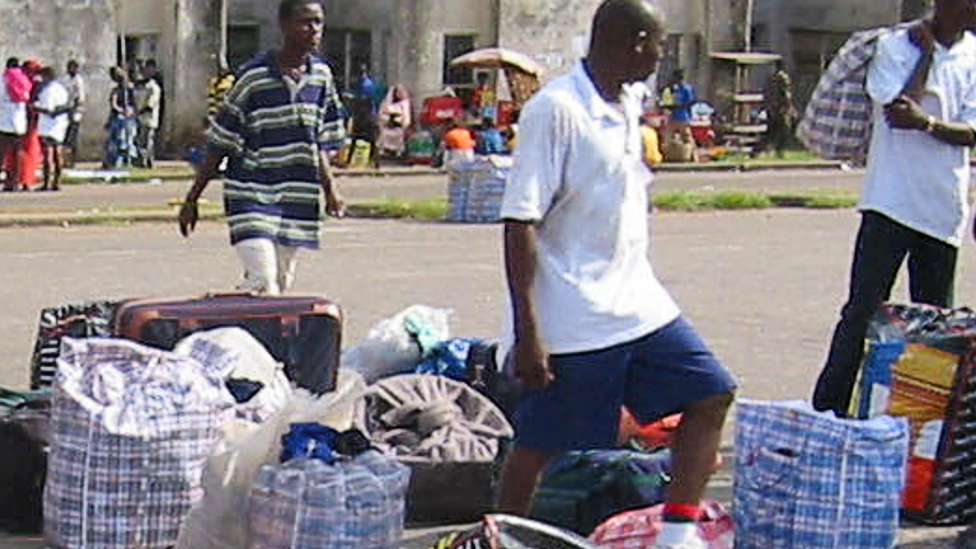 Nigerian returnees and Liberian refugees from war-torn Liberia identify their luggage in Lagos, Nigeria - 20 June 2003