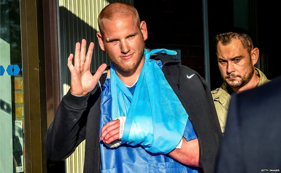 Spencer Stone waves as he leaves hospital in France.