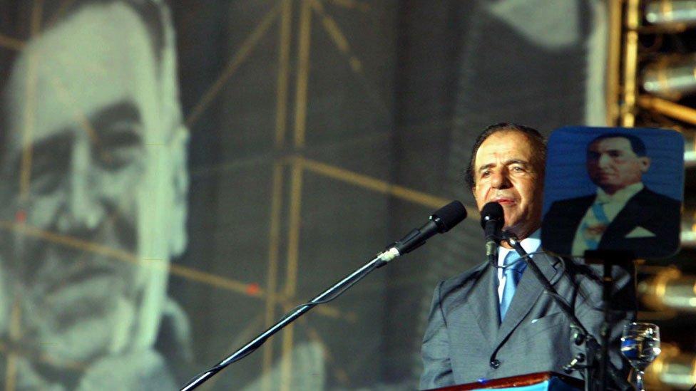 Carlos Menem con dos imágenes de Perón, durante un acto de campaña en 2003