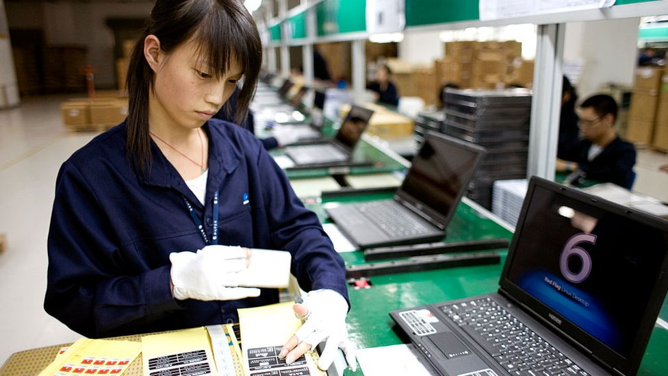 Mujer trabajando en la producción de computadoras chinas.