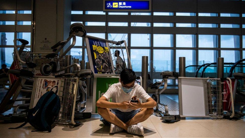Manifestante viendo su teléfono en el aeropuerto