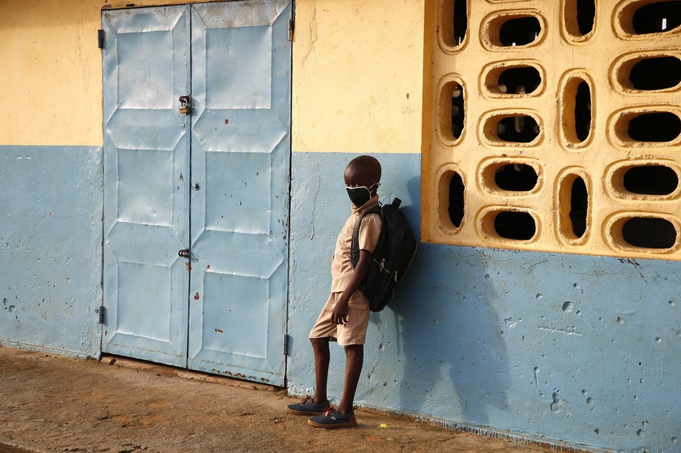 A student wearing a face mask stands outside a classroom.