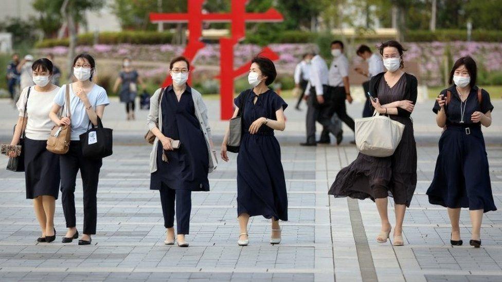 Tokyo'a yürüyen maskeli insanlar