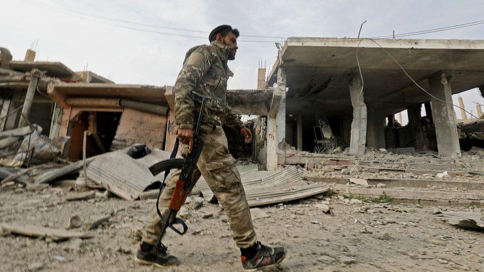 Combatiente sirio caminando por ciudad destrozada