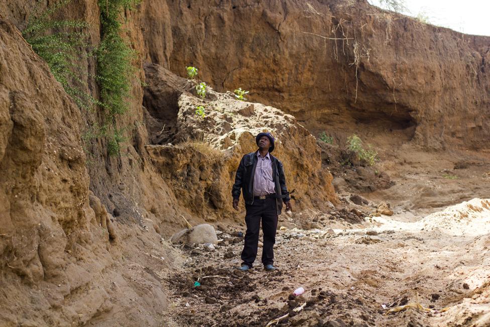 "Anthony Mua Kimeu stares at the steep cliffs of the Kilome Ikolya ""dead"" River"