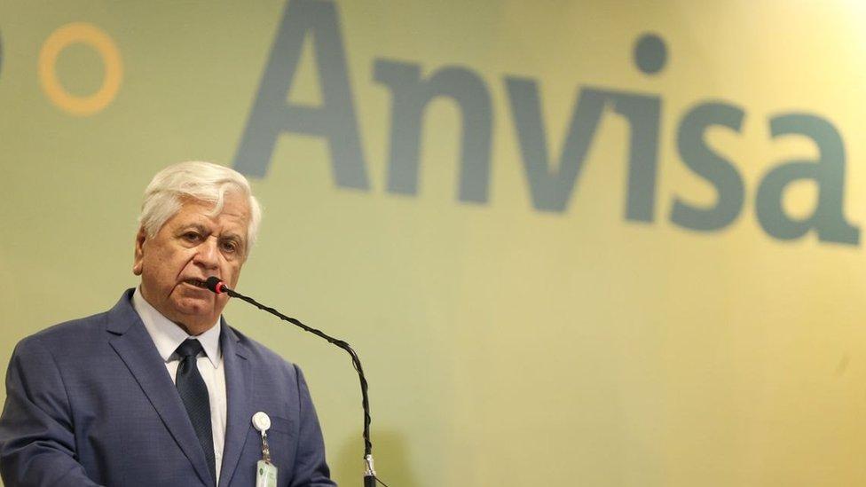 William Dib fala ao microfone, com painel escrito 'Anvisa' atrás