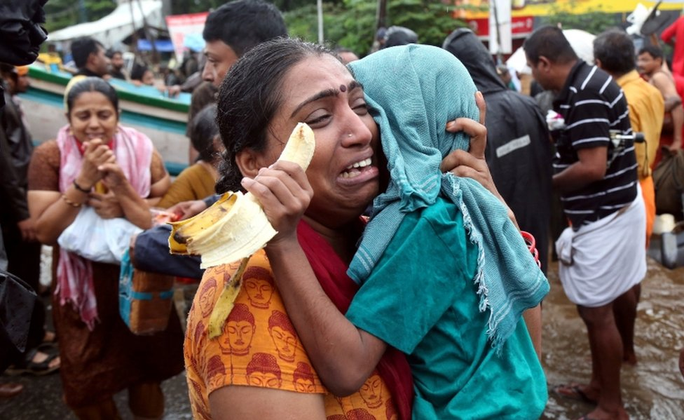 A woman cries as she holds her son after they were evacuated from a flooded area in Aluva, Kerala