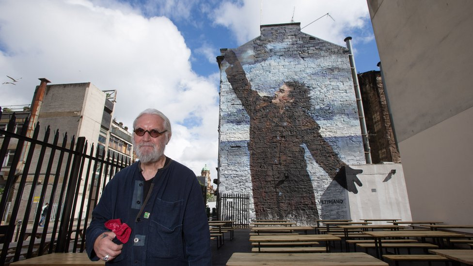 Billy Connolly next to one of his murals