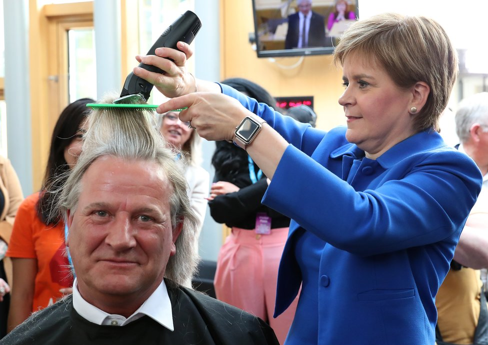 First Minister Nicola Sturgeon cuts the hair of David Torrance SNP MSP