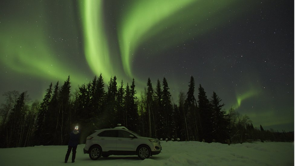 The green light of the Aurora Borealis fills the night sky near North Pole, AK.
