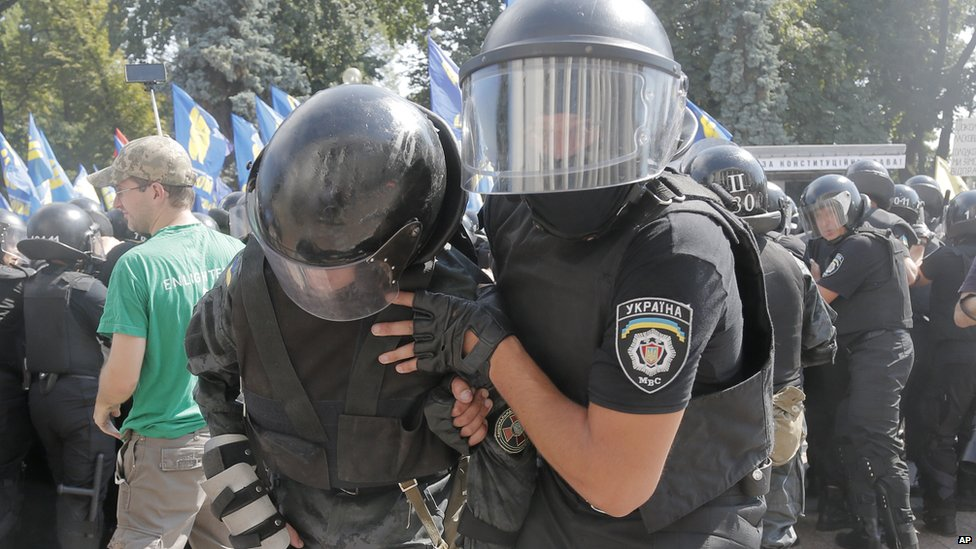 A police officer helps an injured colleague after protests in Kiev